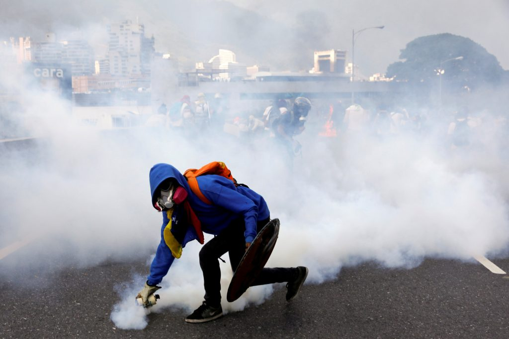 A demonstrator throws back a tear gas canister at police on April 24. Photo by Carlos Garcia Rawlins/Reuters