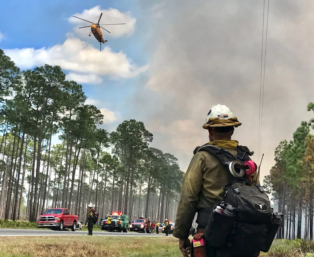 A firefighter watches a helicopter above Georgia Highway 177 as the West Mims fire burns in the Okefenokee National Wildlife Refuge, Georgia, on April 25, 2017. Photo by U.S. Fish and Wildlife Service/Mark Davis via Reuters