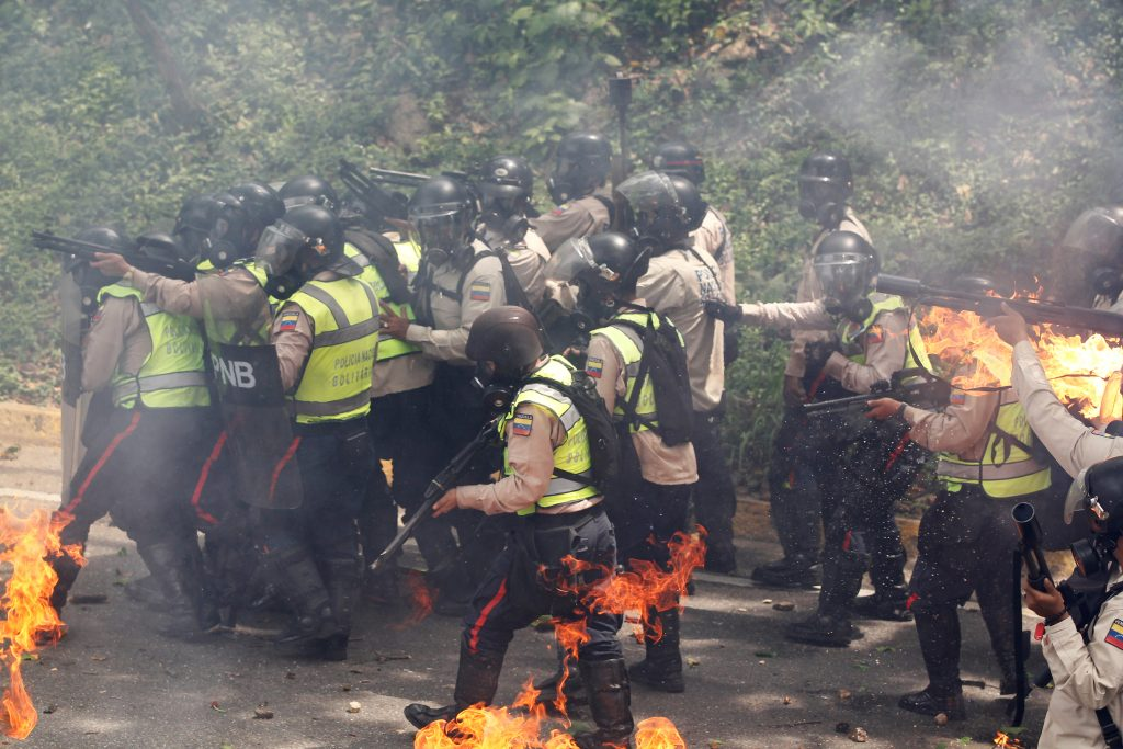 Riot police officers react to fire during one of the rallies. Photo by Christian Veron/Reuters