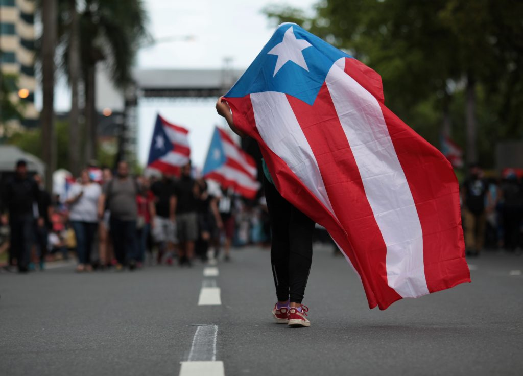 A person carries a Puerto Rican national flag during a protest against the government's austerity measures. Photo by Alvin Baez/Reuters
