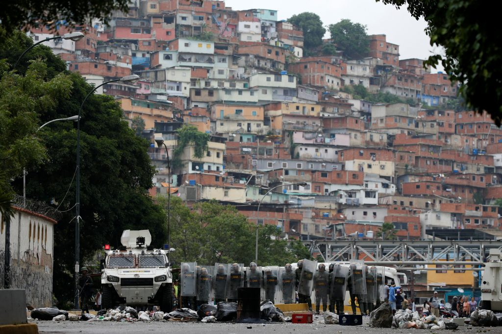 Venezuelan national guards take cover during anti-president protests on May 2. Photo by Carlos Garcia Rawlins/Reuters