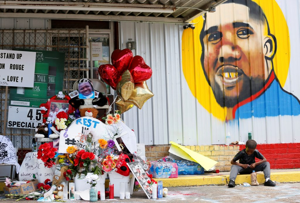 A boy sits next to a makeshift memorial outside the Triple S Food Mart where Alton Sterling was fatally shot by police in Baton Rouge, Louisiana. Photo by Jonathan Bachman/Reuters