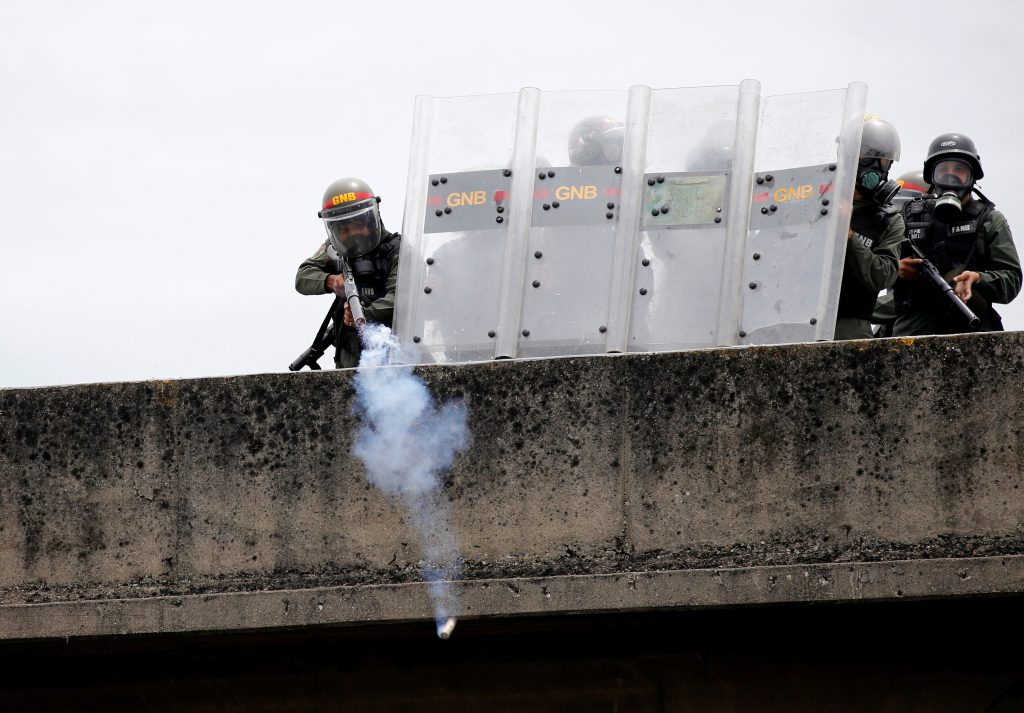 Riot police position themselves on a building during the protests. Photo by Carlos Garcia Rawlins/Reuters