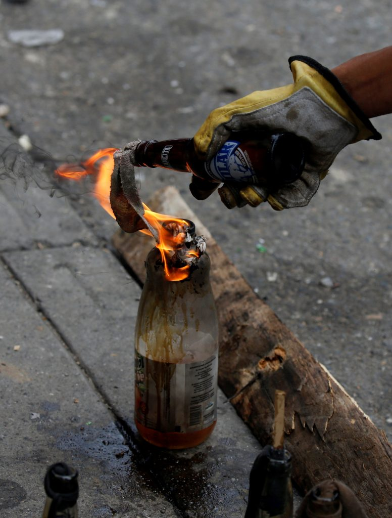 Opposition supporters light a Molotov cocktail while clashing with riot police on May 3. Photo by Carlos Garcia Rawlins/Reuters