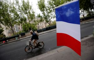A cyclist passes a French flag on the eve of the French presidential election in Paris