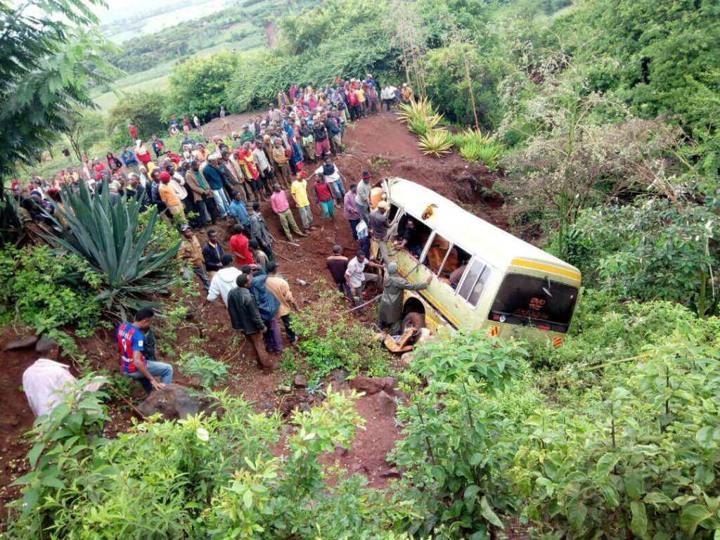 Residents gather at the scene of an accident that killed schoolchildren, teachers and a minibus driver along the Arusha-Karatu highway in Tanzania's northern tourist region of Arusha