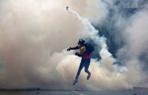 An opposition supporter clashes with riot police during a rally against President Nicolas Maduro in Caracas, Venezuela. Photo by Carlos Garcia Rawlins/Reuters