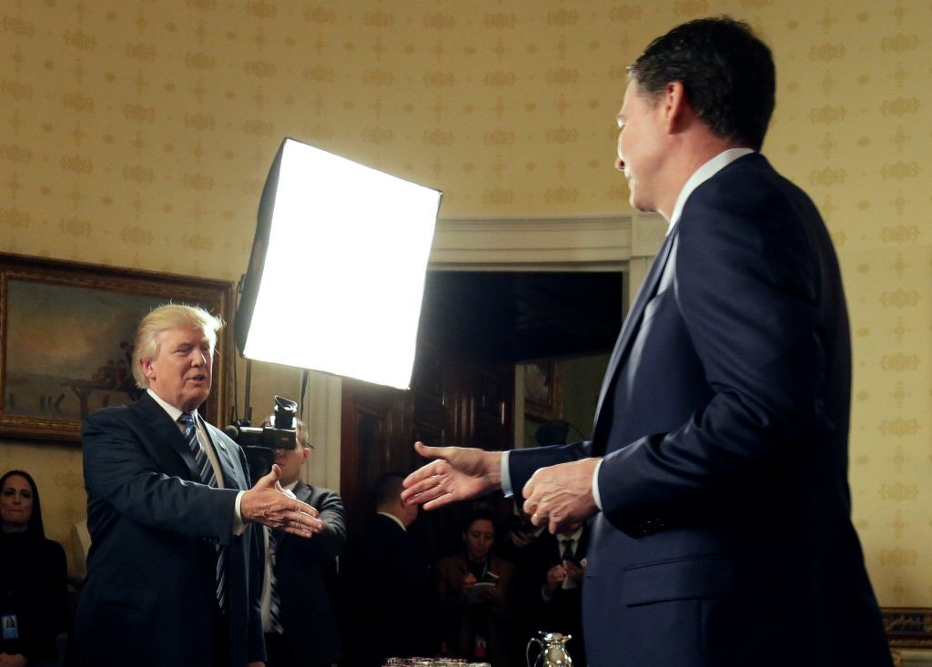 U.S. President Donald Trump greets Director of the FBI James Comey as Director of the Secret Service Joseph Clancy (L) watches during the Inaugural Law Enforcement Officers and First Responders Reception in the Blue Room of the White House in Washington, U.S., January 22, 2017. REUTERS/Joshua Roberts TPX IMAGES OF THE DAY - RTSWV9G