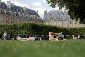 A woman reads a book on the grass on a sunny summer day in the gardens at the Place des Vosges square, with landmark architecture of buildings that date from the seventeenth century, in Paris, August 14, 2013. REUTERS/Christian Hartmann (FRANCE - Tags: CITYSPACE SOCIETY TRAVEL) - RTX12KZJ