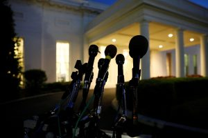 Microphones remain at the ready as night falls on offices and the entrance of the West Wing White House in Washington, D.C. Photo by Jonathan Ernst/Reuters