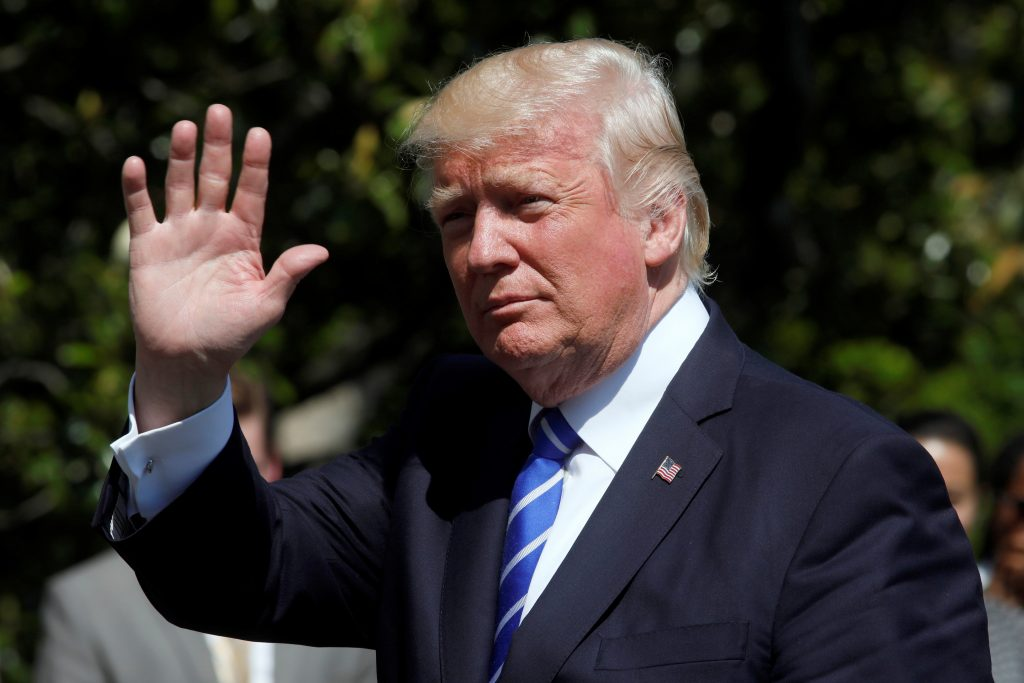 President Donald Trump waves as he walks on the South Lawn of the White House upon his return to Washington, D.C. Photo by...
