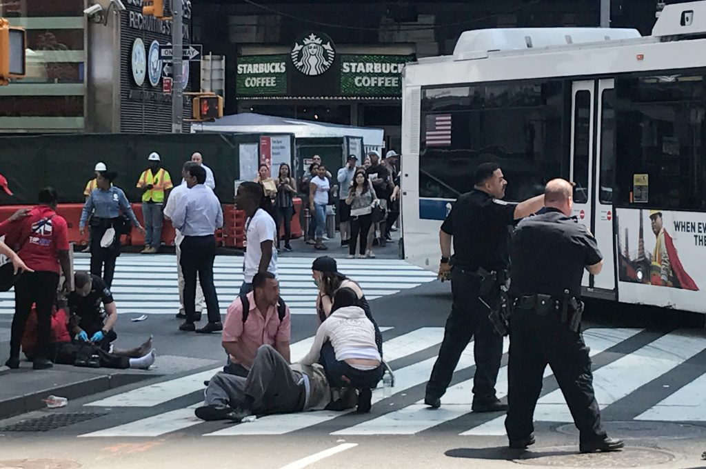 First responders are at the scene as people help injured pedestrians after a vehicle struck pedestrians on a sidewalk in Times Square in New York, U.S., May 18, 2017. REUTERS/Jeremy Schultz - RTX36FU8