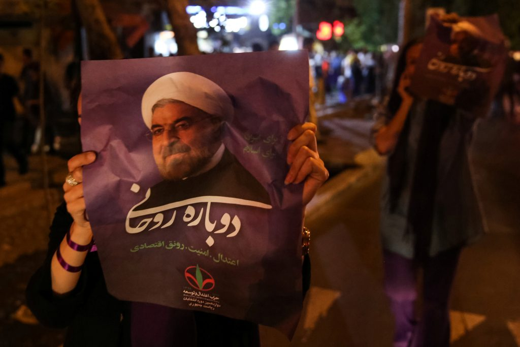 A supporter of Iranian president Hassan Rouhani holds his poster as she celebrates his victory in the presidential election, in Tehran