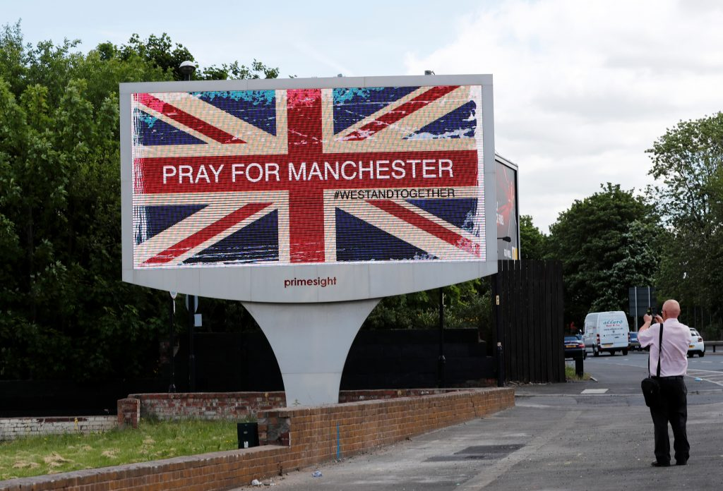 A man photographs a sign in Manchester, Britain. Photo by Stefan Wermuth/Reuters