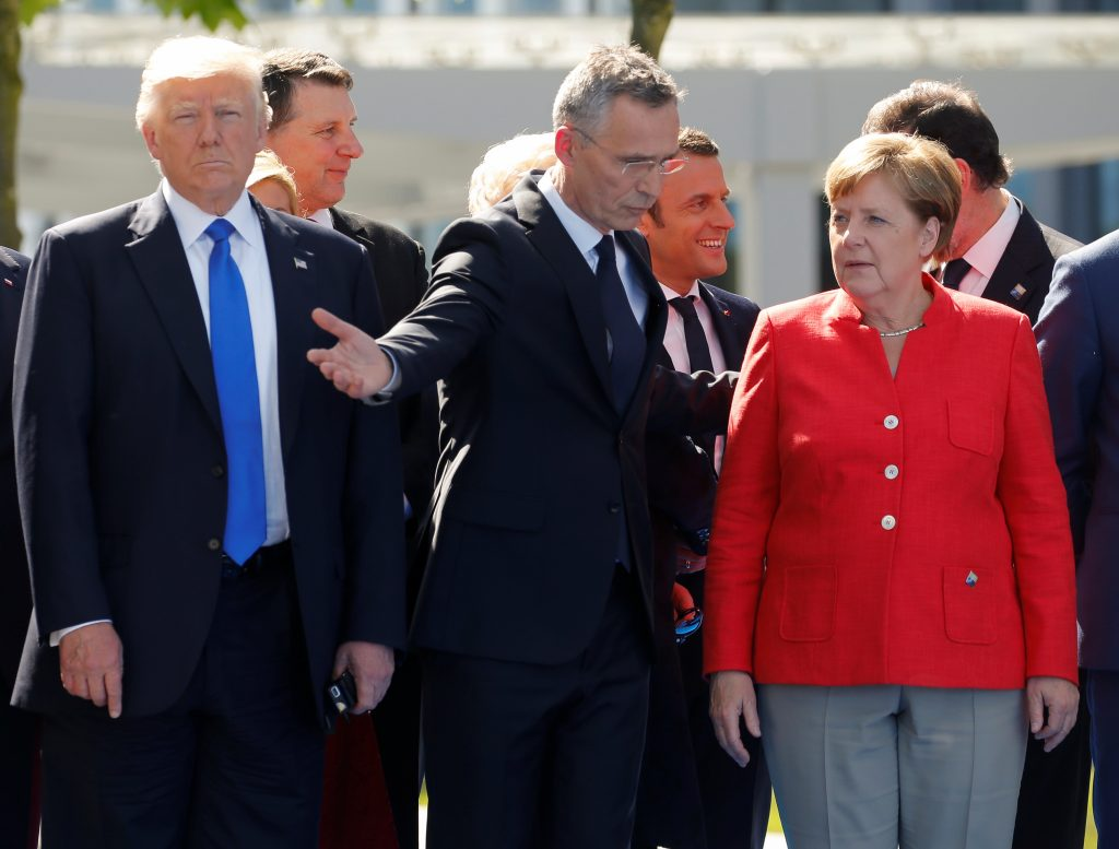 (L-R) U.S. President Donald Trump, NATO Secretary General Jens Stoltenberg and German Chancellor Angela Merkel gather with NATO member leaders to pose for a family picture before the start of their summit in Brussels, Belgium, May 25, 2017.REUTERS/Jonathan Ernst - RTX37LMV