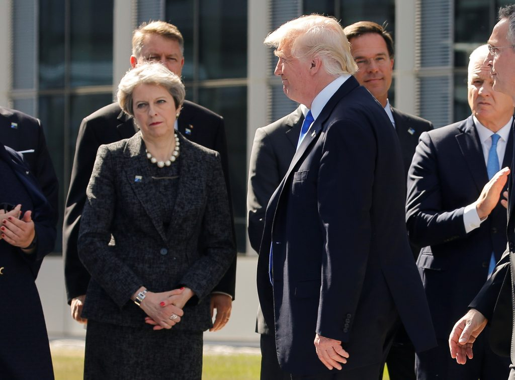 U.S. President Donald Trump (R) walks past Britain's Prime Minister Theresa May at the start of the NATO summit at their new headquarters in Brussels, Belgium, May 25, 2017. REUTERS/Jonathan Ernst - RTX37LSW