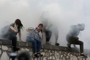 Demonstrators run away from tear gas during a demonstration against the G7 summit in Giardini Naxos