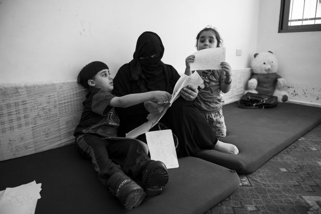 Mustafa and Doaa show their grandmother their drawings. Photo by Sebastian Rich