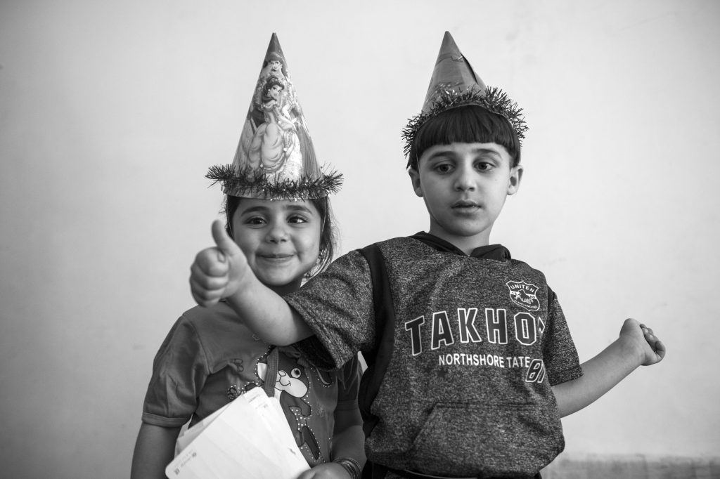 Mustafa and Doaa play with party hats at the Homs league project. Photo by Sebastian Rich