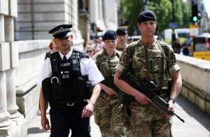 Soldiers walk with a police officer on Whitehall in London, Britain May 24, 2017. REUTERS/Neil Hall - RTX37E6F