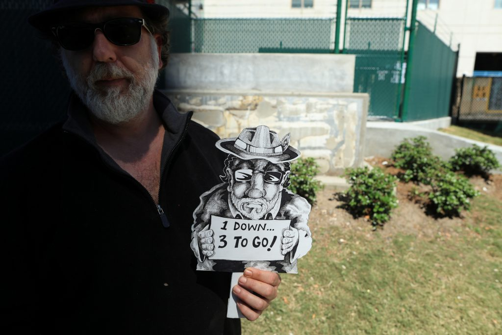 Thom Karamus, a New Orleans artist, stands with a sign he made in front of the former home of the Battle of Liberty Place monument, built in 1891 to commemorate a battle between the Crescent City White League and New Orleans biracial police force. It was removed April 24, one of four Confederate monuments the city of New Orleans was taking down last week. Photo by REUTERS/Ben Depp.
