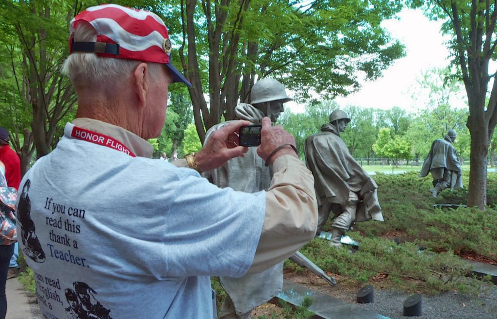 A veteran takes a snapshot of the Korean War memorial in Washington, D.C. Photo by Larisa Epatko/PBS NewsHour