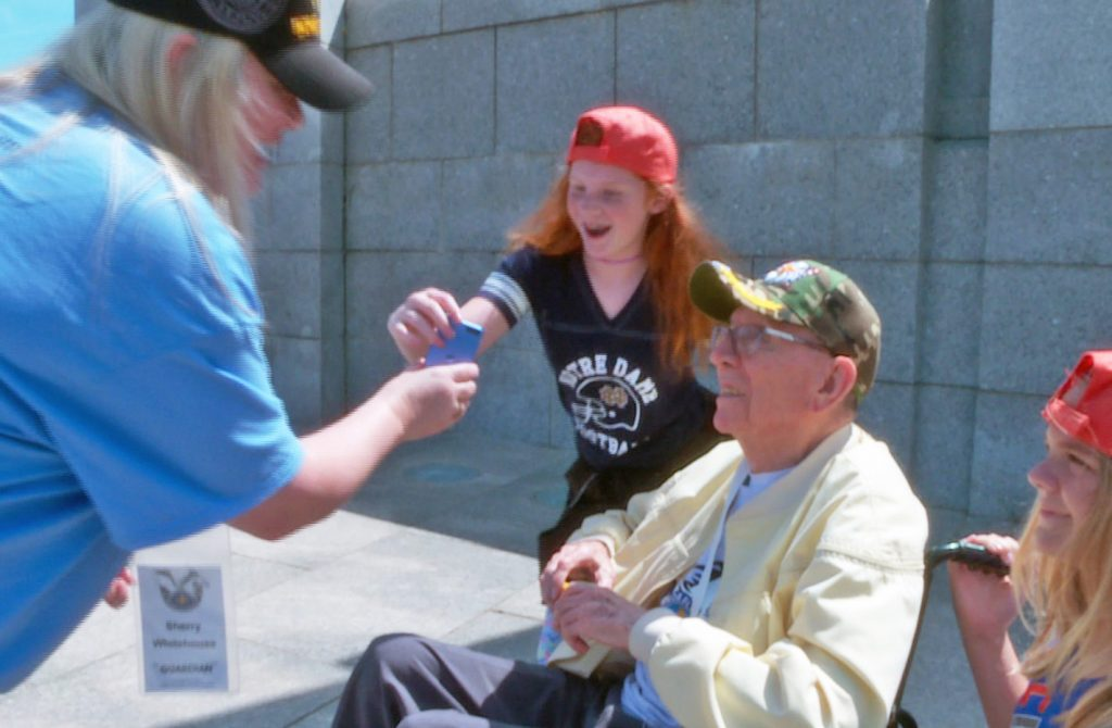 Some admirers get their picture taken with one of the visiting Kentucky veterans. Photo by Larisa Epatko/PBS NewsHour