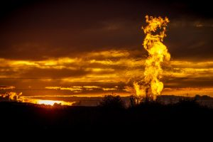 Flames from a flaring pit near a well in the Bakken Oil Field. The primary component of natural gas is methane, which is odorless when it comes directly out of the gas well. In addition to methane, natural gas typically contains other hydrocarbons such as ethane, propane, butane, and pentanes. Raw natural gas may also contain water vapor, hydrogen sulfide (H2S), carbon dioxide, helium, nitrogen, and other compounds. (Source: www.earthworksaction.org). As of July 2014, roughly 30 percent of the Photo by Orjan F. Ellingvag/Corbis via Getty Images