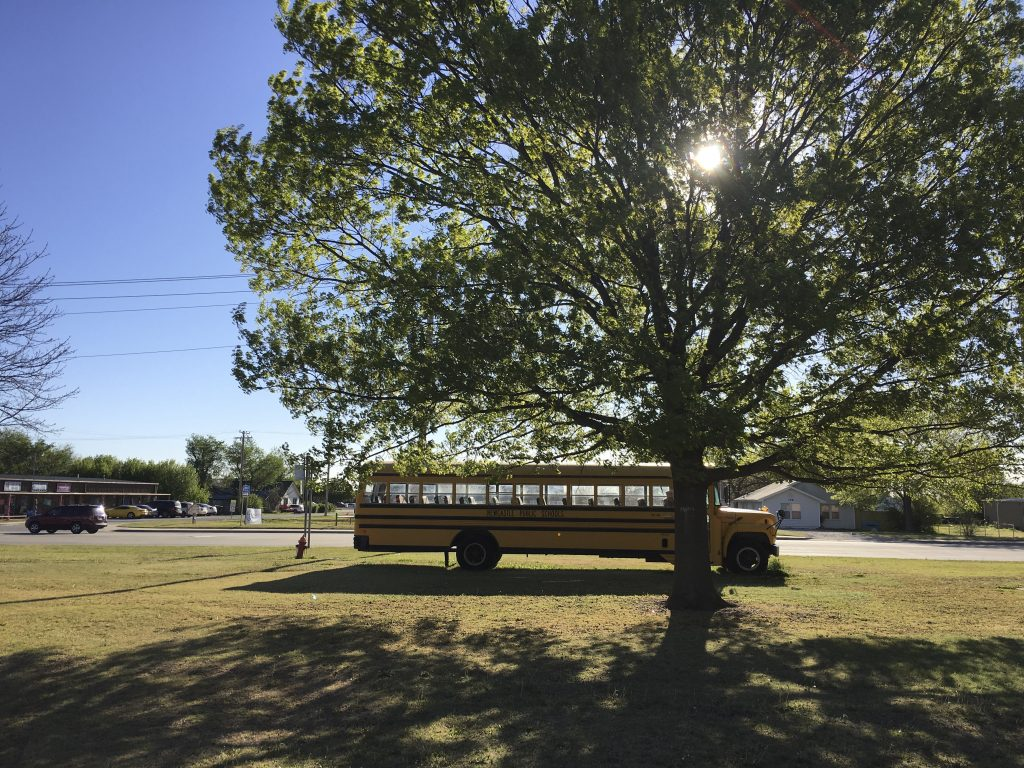 A Newcastle Public Schools bus is seen parked in Newcastle, Oklahoma April 6, 2016. The Newcastle schools are planning to reduce the school week to four days next year as a result of a nearly $1 million budget cut. REUTERS/Luc Cohen - RTSEOHN