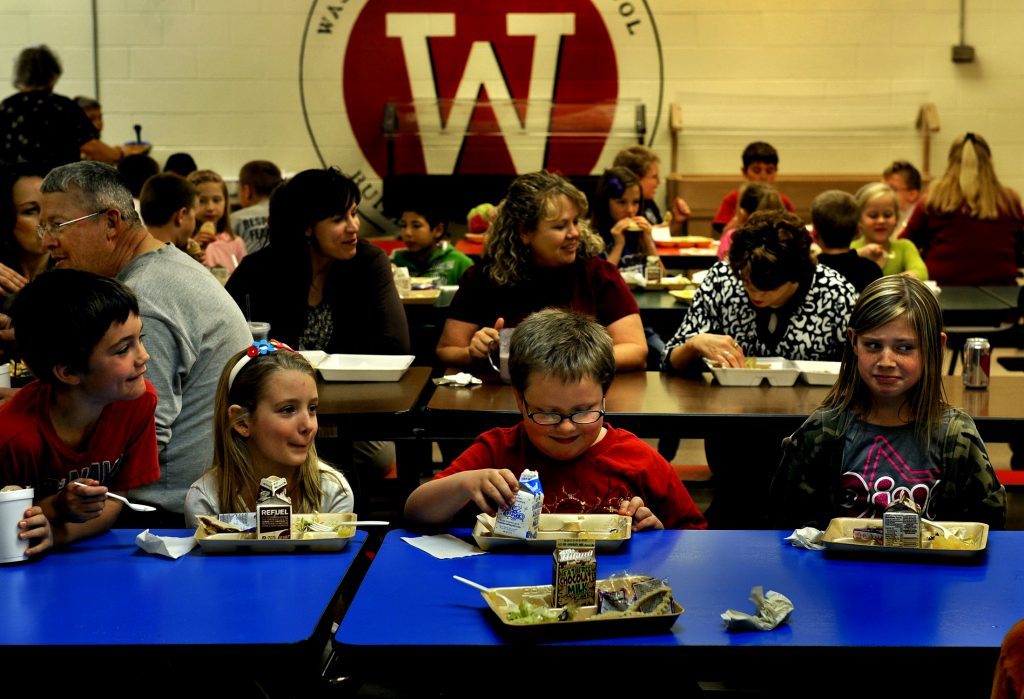 Students and teachers sit and eat together in this file photo at the Washington Elementary School cafeteria in Washington, Okla. Photo by Michael S.Williamson/The Washington Post via Getty Images.