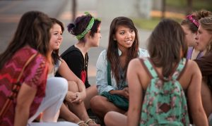 Female students talking outdoors on the sidewalk. Photo by Scott Griessel/via Adobe