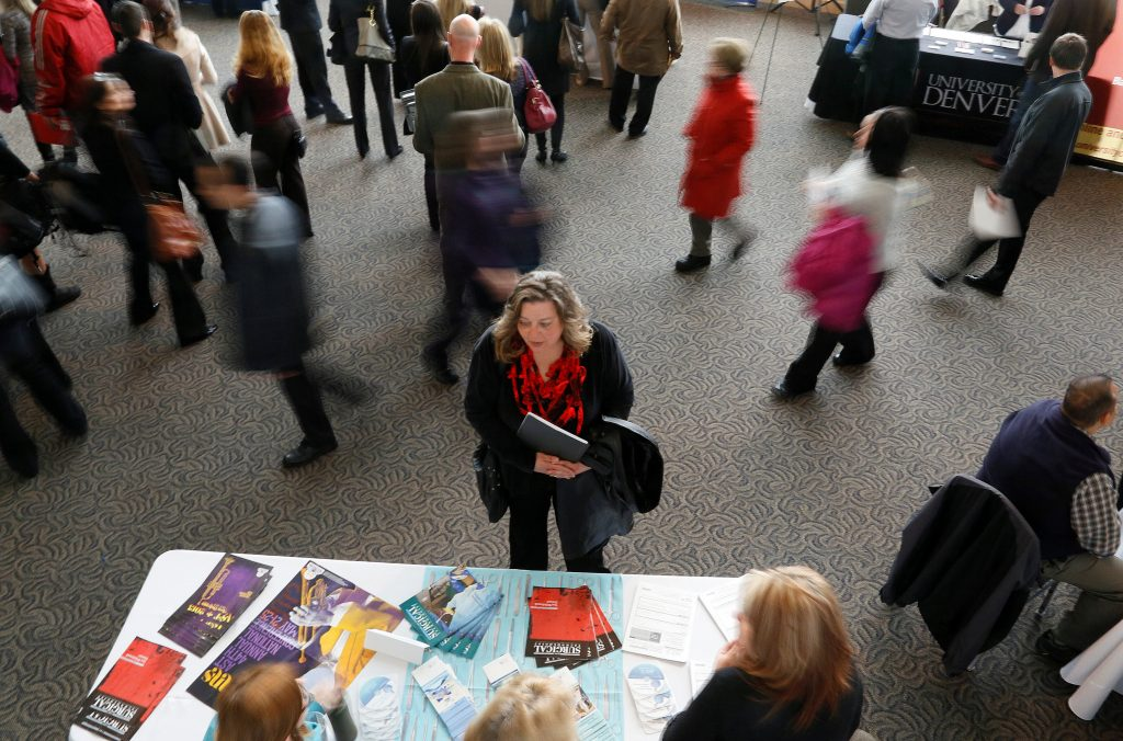 FILE PHOTO: A job seeker talks to an exhibitor at the Colorado Hospital Association health care career fair in Denver