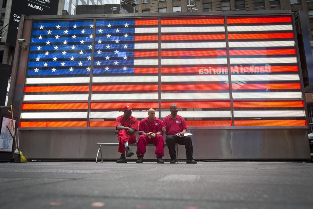 A street sweeping crew takes a break in front of a U.S. flag on Independence Day in Times Square in New York July 4, 2014. REUTERS/Carlo Allegri (UNITED STATES - Tags: SOCIETY) - RTR3X4CX