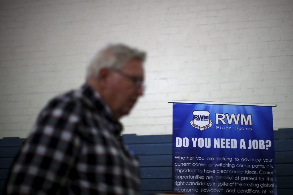 A job seeker walks past a sign at a veterans' job fair in Burbank, Los Angeles, California March 19, 2015. The number of Americans filing new claims for unemployment benefits rose marginally last week, indicating the labor market remained on solid footing despite slowing economic growth. REUTERS/Lucy Nicholson - RTR4U3N5