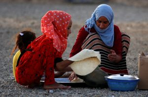 Evacuees make bread inside a refugee camp in Erbil, Iraq, for people who fled from Mosul due to fighting between Iraqi forces and Islamic State militants. Photo by Erik De Castro/Reuters