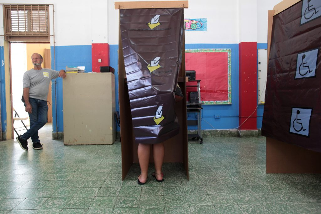 A woman leaves a voting booth as Puerto Ricans head to the polls on Sunday to decide whether they want their struggling U.S. territory to become the 51st U.S. state, in San Juan, Puerto Rico. Photo by Alvin Baez/Reuters