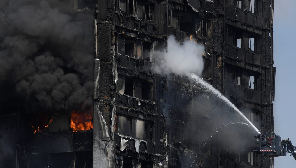 Firefighters direct jets of water onto a tower block severely damaged by a serious fire in north Kensington, West London o...
