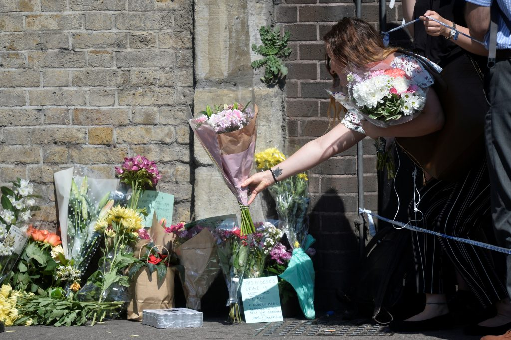 A woman leaves flowers near the scene of an attack where a van was driven at muslims outside a mosque in Finsbury Park in North London, Britain, June 19, 2017. REUTERS/Hannah McKay - RTS17O6F