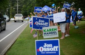 Supporters for Georgia 6th Congressional District Democratic candidate Jon Ossoff rally and wave at passing cars amid signs for Republican candidate Karen Handel outside St Mary's Orthodox Church, Handel's polling place in Roswell, Georgia, U.S., June 20, 2017. REUTERS/Bita Honarvar - RTS17VZQ