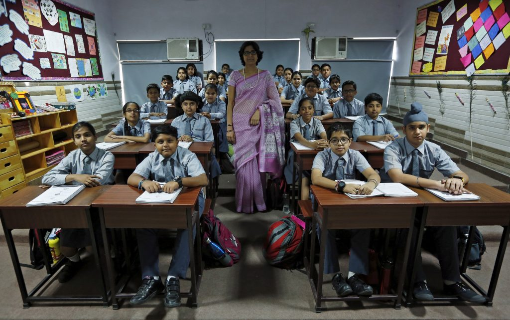 A teacher poses for a picture with seventh-grade level students inside their classroom at Rukmini Devi Public school in New Delhi, India. Photo taken in 2015. Photo by Adnan Abidi/Reuters