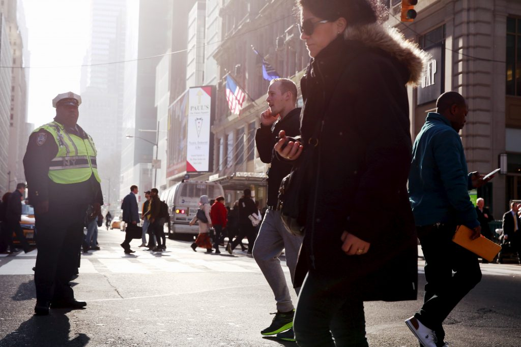 Morning commuters cross the street as the sun shines down 42nd St i…