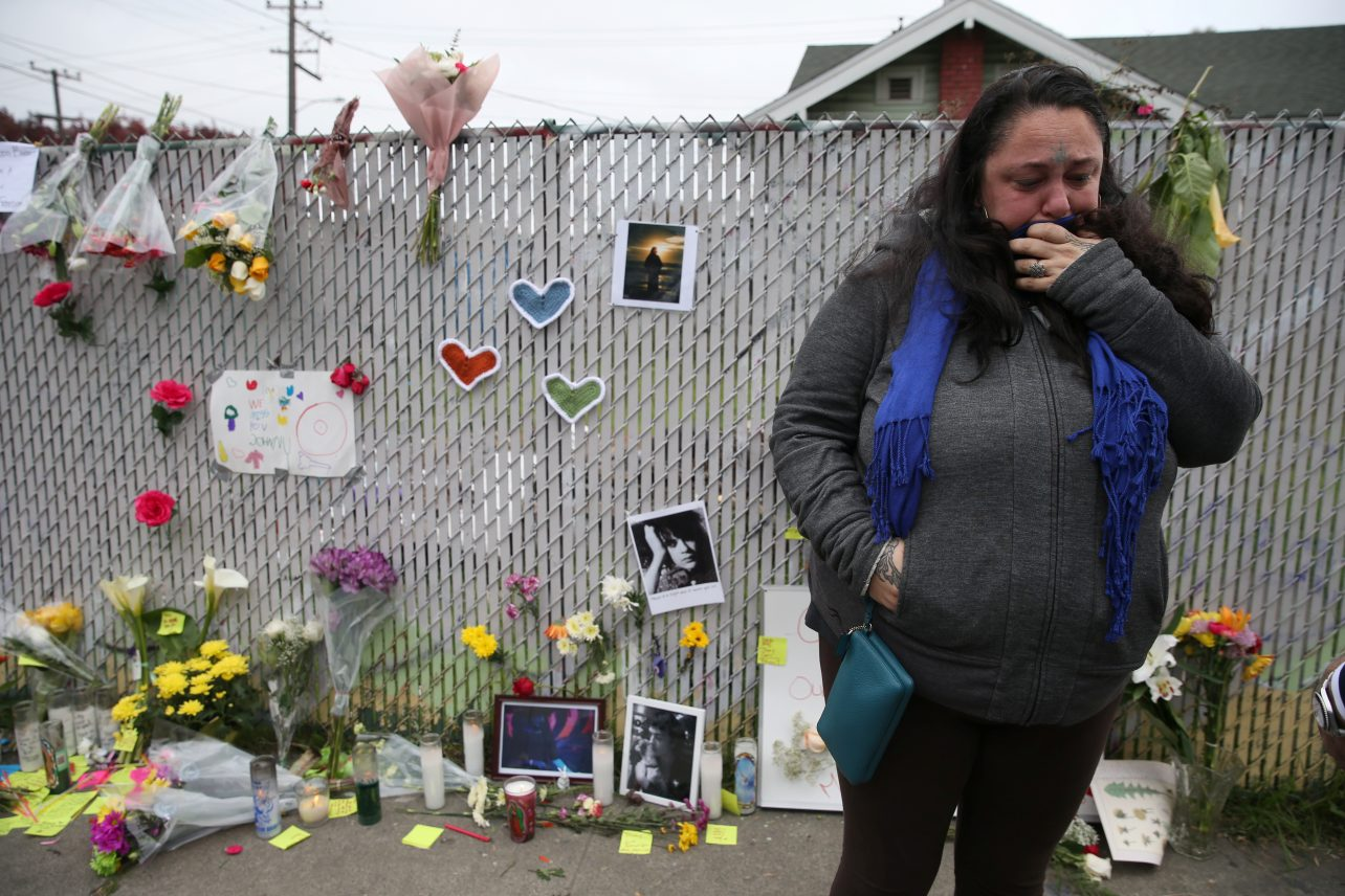 Danielle Boudreaux, 40, who knew Derick Ion Almena and his children and went to the Ghost Ship many times, cries at a sidewalk memorial near the burned warehouse following the fatal fire in the Fruitvale district of Oakland