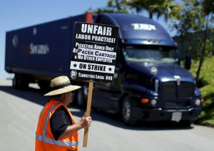 A striking truck driver walks a picket line at a Pacer Cartage facility in Otay Mesa, California