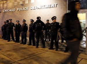 A protester walks past a line of police officers standing guard in front of the District 1 police headquarters in Chicago on Nov. 24, 2015. Photo by Frank Polich/Reuters