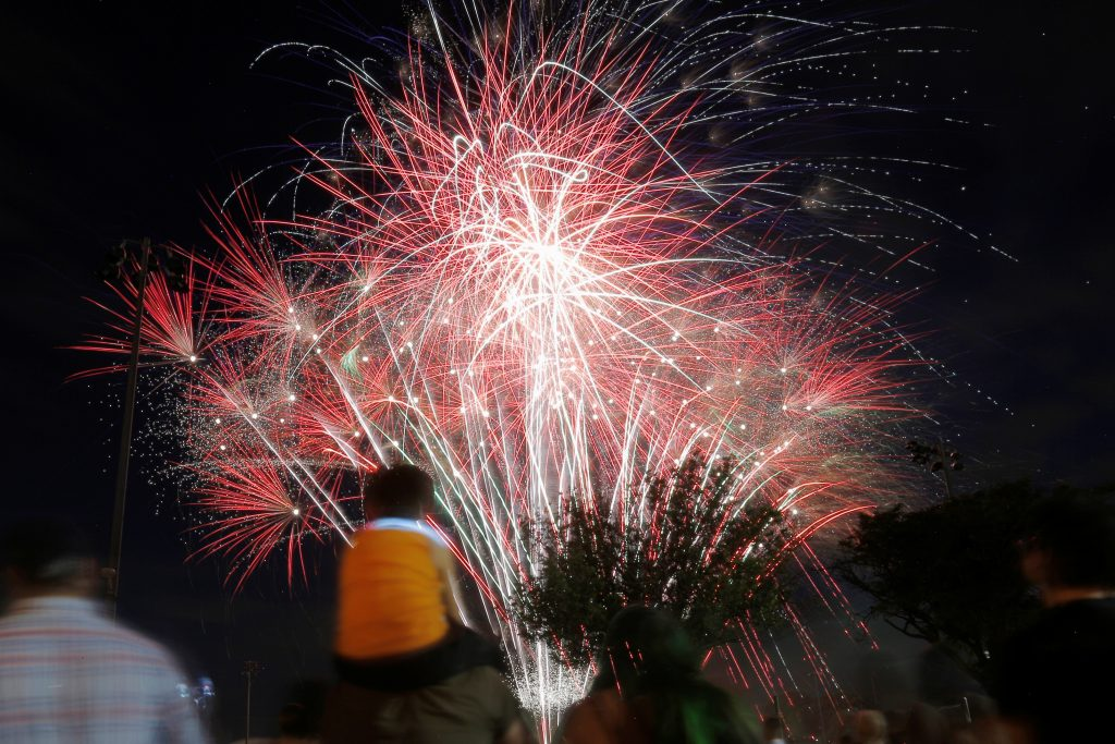 A boy watches the fireworks from his father's shoulders during U.S. Independence Day celebrations in Somerville, Massachusetts June 30, 2016, ahead of the July 4th holiday. REUTERS/Brian Snyder - RTX2J5J3