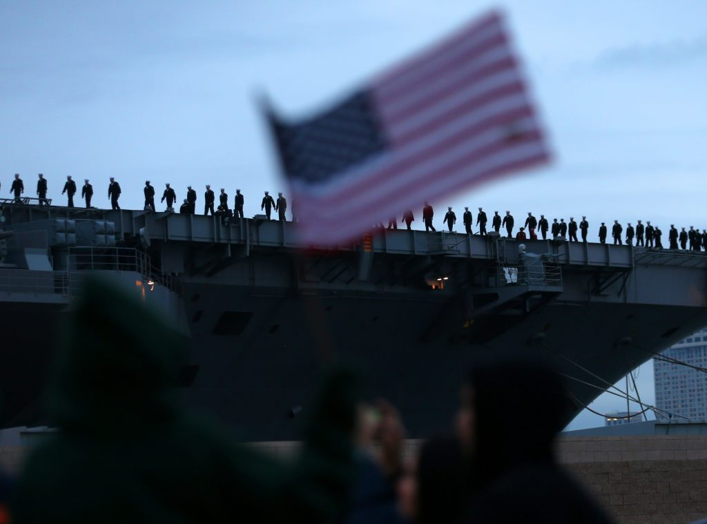 Sailors man the rails onboard the USS Carl Vinson aircraft carrier as they depart on deployment from Naval Station North Island in Coronado, California. Photo by Mike Blake/Reuters