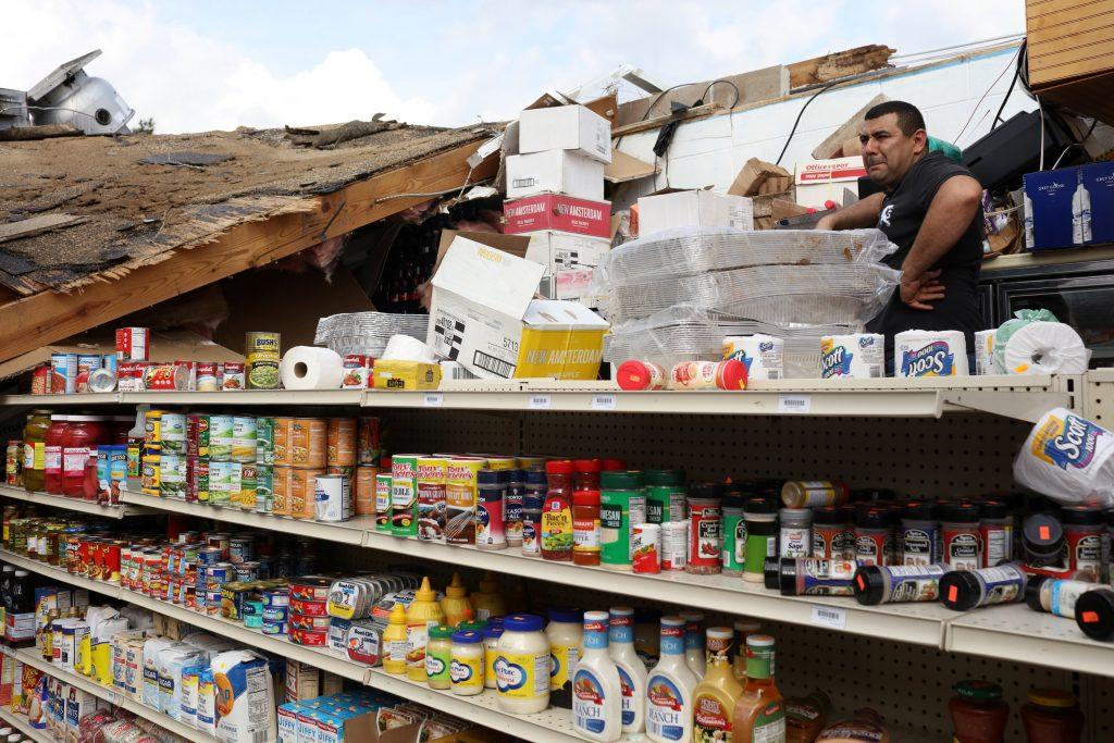 Abdel Salah, the owner of Sam's Food and Liquor Store surveys damag…