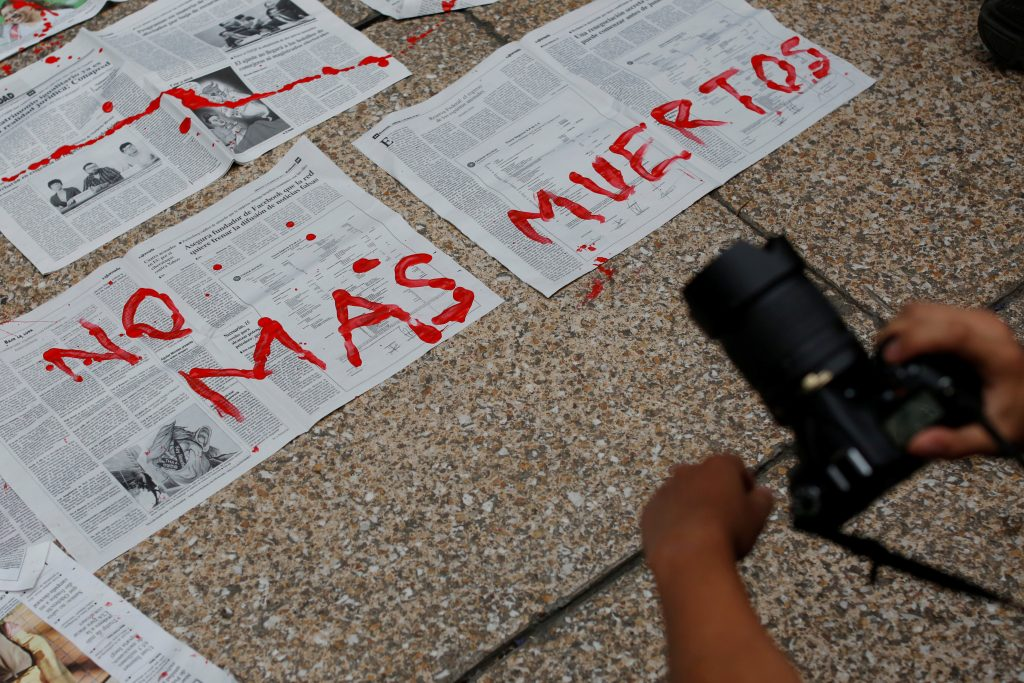 Journalists and activist paint on news papers with fake blood during a protest against the murder of the Mexican journalist Miroslava Breach