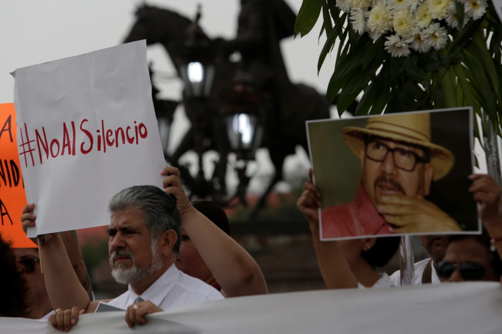 Demonstrators hold up a sign and a picture of journalist killed Javier Valdez during a demonstration against the murder of...