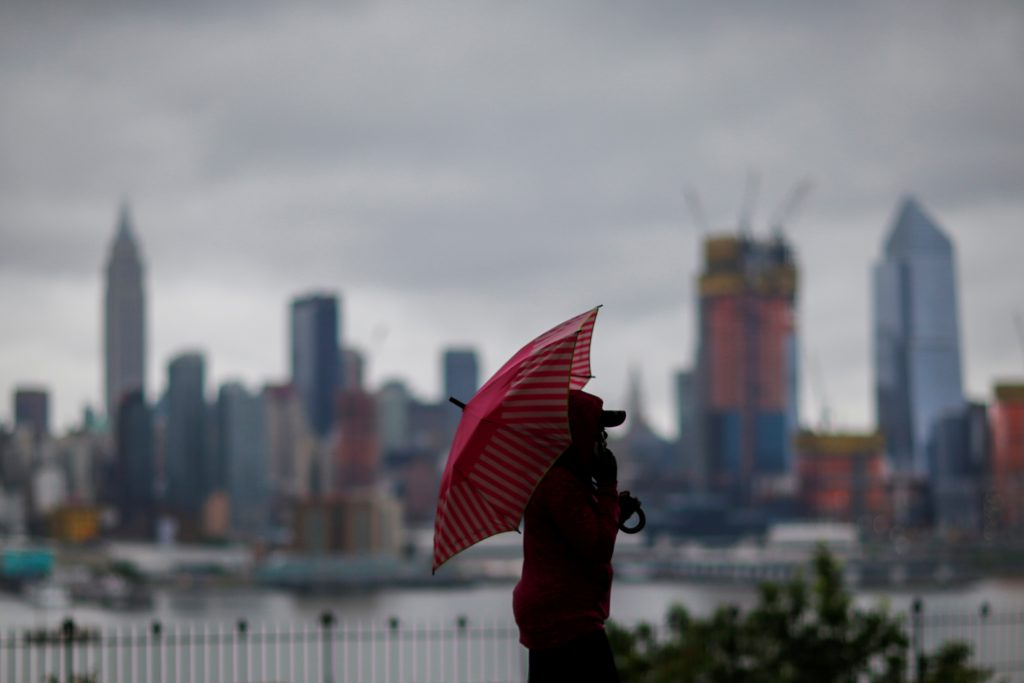 A woman walks in a local park while clouds shroud the Empire State Building and the skyline of New York as it is seen from Weehawken, New Jersey, U.S. May 29, 2017. REUTERS/Eduardo Munoz - RTX384B4